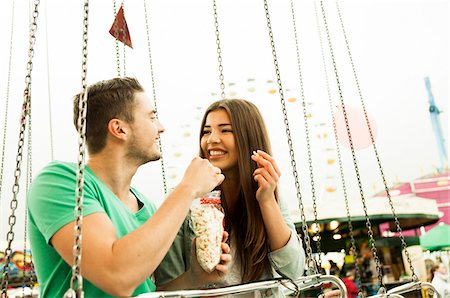Young couple sitting on amusement park ride eating popcorn, Germany Stock Photo - Premium Royalty-Free, Code: 600-07156196