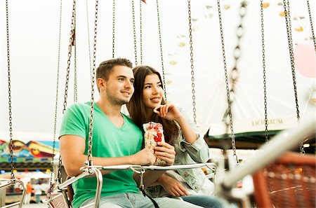 Young couple sitting on amusement park ride eating popcorn, Germany Stock Photo - Premium Royalty-Free, Code: 600-07156197