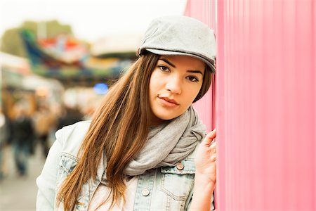 Close-up portrait of teenage girl wearing hat at amusement park, looking at camera, Germany Stock Photo - Premium Royalty-Free, Code: 600-07156192