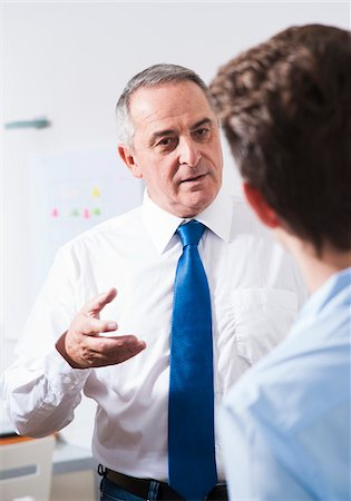 Businessman explaining work to apprentice in office, Germany Stock Photo - Premium Royalty-Free, Code: 600-07199804