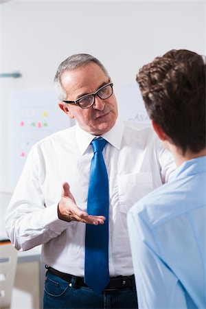 Businessman explaining work to apprentice in office, Germany Stock Photo - Premium Royalty-Free, Code: 600-07199806