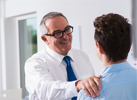 supervising - Businessman with hand on shoulder of apprentice in office, Germany Stock Photo - Premium Royalty-Free, Code: 600-07199807