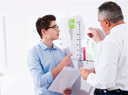 Businessman explaining chart to apprentice in office, Germany Stock Photo - Premium Royalty-Free, Code: 600-07199809