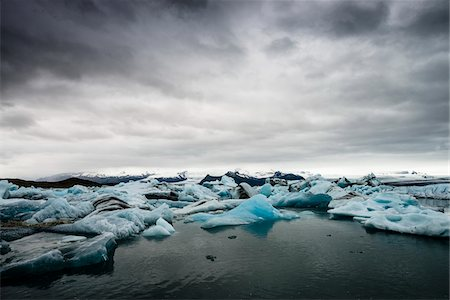 extreme terrain - View of the lagoon Jokulsarlon glacial lake, landscape with reflections on the sea, blue iceberg and sky with gray clouds, Jokulsarlon, Skaftafell, Iceland, Europe Stock Photo - Premium Royalty-Free, Code: 600-07199800