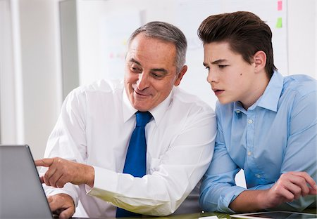 Businessman showing computer data to apprentice in office, Germany Stock Photo - Premium Royalty-Free, Code: 600-07199802