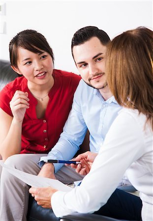 Backview of businesswoman in discussion with young couple, Germany Stock Photo - Premium Royalty-Free, Code: 600-07199924