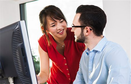Close-up of young businessman and young businesswoman having a discussion in front of a computer in office, Germany Stock Photo - Premium Royalty-Free, Code: 600-07199954