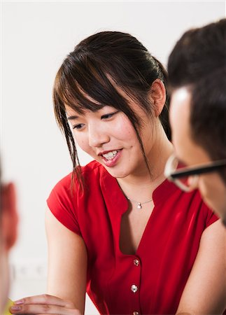 Close-up of young businesswoman in discussion with young businessman, Germany Stock Photo - Premium Royalty-Free, Code: 600-07199956