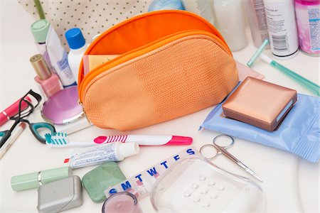 Women's Toiletry Travel Bag on Bathroom Counter filled with Personal Hygiene Products Stock Photo - Premium Royalty-Free, Code: 600-07232302
