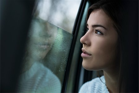 Portrait of young woman sitting inside car and looking out of window and day dreaming on overcast day, Germany Stock Photo - Premium Royalty-Free, Code: 600-07278926