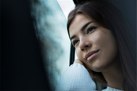 Portrait of young woman sitting inside car and looking out of window and day dreaming on overcast day, Germany Stock Photo - Premium Royalty-Free, Code: 600-07278928