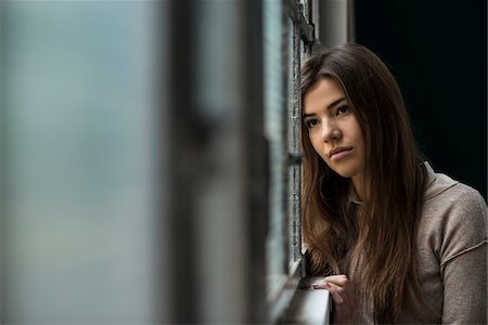 Portrait of young woman standing in front of window, day dreaming and looking into the distance, Germany Stock Photo - Premium Royalty-Free, Code: 600-07278937