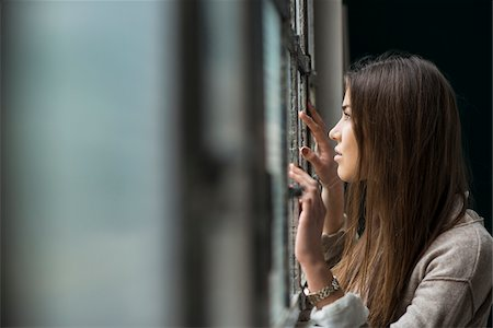 Portrait of young woman standing and looking out of window day dreaming, Germany Stock Photo - Premium Royalty-Free, Code: 600-07278938