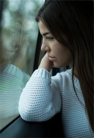 Portrait of young woman sitting inside car and looking out of window and day dreaming on overcast day, Germany Stock Photo - Premium Royalty-Free, Code: 600-07278930