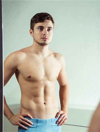 perception - Portrait of young man looking at reflection in bathroom mirror with hands on hips, studio shot Stock Photo - Premium Royalty-Free, Code: 600-07278946