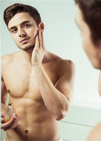perception - Close-up of young man looking in bathroom mirror applying cologne to face, studio shot Stock Photo - Premium Royalty-Free, Code: 600-07278948