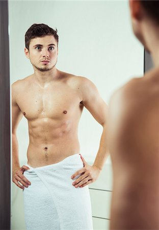 perception - Portrait of young man with towel wrapped around waist, looking in bathroom mirror, studio shot Stock Photo - Premium Royalty-Free, Code: 600-07278953