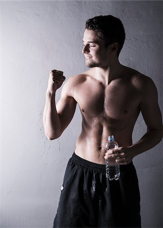Young man pumping fist and holding bottle of water after working out, studio shot on grey background Stock Photo - Premium Royalty-Free, Code: 600-07278963