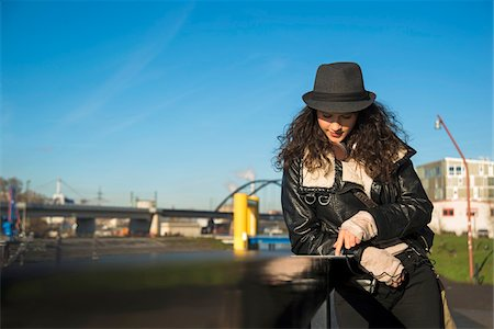 Teenage girl standing outdoors, wearing fedora and using tablet computer, Germany Stock Photo - Premium Royalty-Free, Code: 600-07310987