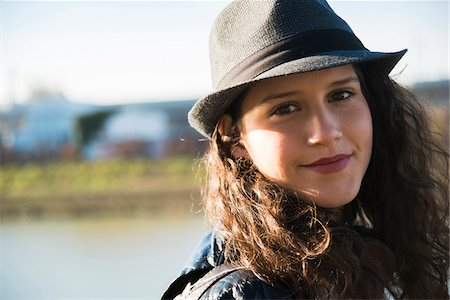 pretty - Close-up portrait of teenage girl outdoors, wearing fedora, smiling and looking at camera, Germany Stock Photo - Premium Royalty-Free, Code: 600-07310989