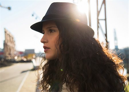 Close-up portrait of teenage girl outdoors, wearing fedora and looking into the distance, Germany Stock Photo - Premium Royalty-Free, Code: 600-07310993