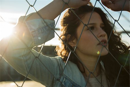restrained - Close-up portrait of teenage girl standing outdoors next to chain link fence, Germany Stock Photo - Premium Royalty-Free, Code: 600-07311006