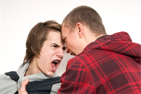 Close-up of two teenage boys fighting and screaming at each other, studio shot on white background Stock Photo - Premium Royalty-Free, Code: 600-07311024