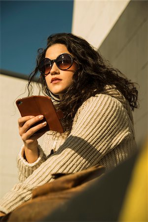 Close-up portrait of teenage girl outdoors wearing sunglasses, sitting next to building and holding smart phone, Germany Stock Photo - Premium Royalty-Free, Code: 600-07311098