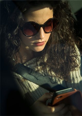 Close-up of teenage girl sitting in car, wearing sunglasses and looking down at smart phone, Germany Stock Photo - Premium Royalty-Free, Code: 600-07311092
