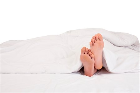 female feet close up - Bare feet sticking out of blanket on bed, studio shot on white background Stock Photo - Premium Royalty-Free, Code: 600-07311108