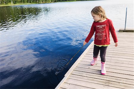 3 year old girl in red shirt on a pier holding a stick and playing in the water, Sweden Stock Photo - Premium Royalty-Free, Code: 600-07311126