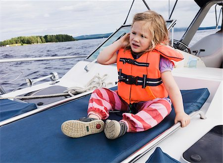 sole - 3 year old girl in orange life jacket sitting on top of motorboat, Sweden Stock Photo - Premium Royalty-Free, Code: 600-07311130