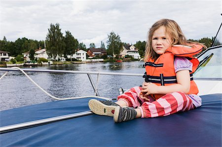 sole - 3 year old girl in orange life jacket sitting on top of motorboat, docked on lake, Sweden Stock Photo - Premium Royalty-Free, Code: 600-07311131
