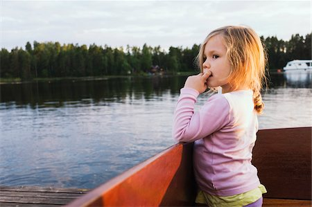 3 year old girl standing in a docked motorboat, looking at the lake, Sweden Stock Photo - Premium Royalty-Free, Code: 600-07311132