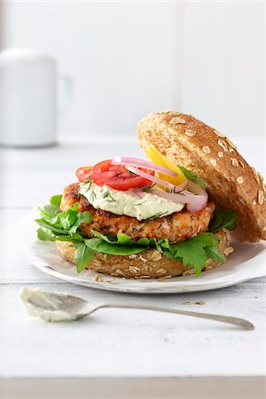 Salmon burger on a whole wheat bun with lettuce, red onion, red tomatoes, yellow tomatoes, sauce, and fresh dill on a white tabletop in a high key setting Stock Photo - Premium Royalty-Free, Code: 600-07311148
