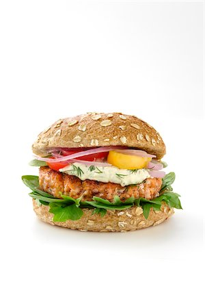 Salmon burger on a whole wheat bun with lettuce, red onion, red tomatoes, yellow tomatoes, sauce, and fresh dill isolated on a white background. Stock Photo - Premium Royalty-Free, Code: 600-07311149