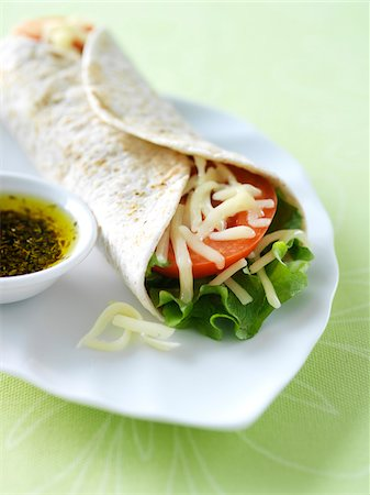 Vegetarian soft taco wrap with lettuce, tomato, and monterey jack cheese on a white plate with herbed olive oil on the side. Stock Photo - Premium Royalty-Free, Code: 600-07311156