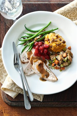 Overhead image of a holiday dinner plate containing turkey breast, gravy, stuffing, sweet potato, green beans, cranberries, walnuts and fresh rosemary. Cutlery, ice water, and a napkin are also present on a wooden cutting board on a table top. Stock Photo - Premium Royalty-Free, Code: 600-07311152
