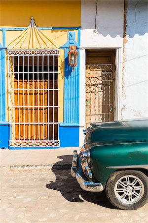 Vintage car on a cobblestone street by colorful wall of house, UNESCO World Heritage Site, Trinidad, Cuba Stock Photo - Premium Royalty-Free, Code: 600-07311177