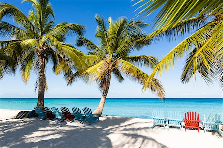 Beach chairs under coconut palm trees on the white beach by turquoise clear water, Del Este National Park (Parque Nacional del Este), Dominican Republic, Caribbean Stock Photo - Premium Royalty-Free, Code: 600-07311200
