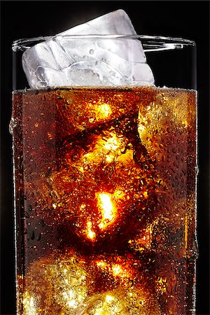 Glass of Soda with Ice Cubes on Black Background Stock Photo - Premium Royalty-Free, Code: 600-07311270