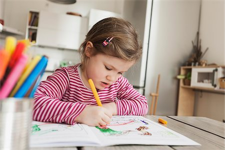 Girl Sitting at Table and Colouring Pictures Stock Photo - Premium Royalty-Free, Code: 600-07311314