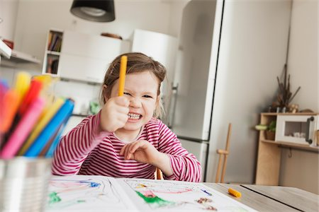 Girl Sitting at Table Colouring Pictures and Pointing Marker to the Camera Stock Photo - Premium Royalty-Free, Code: 600-07311313