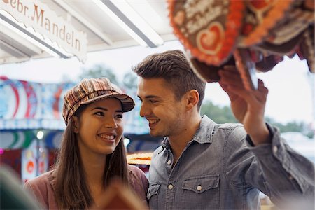 purchase - Close-up of young couple having fun at amusement park, Germany Stock Photo - Premium Royalty-Free, Code: 600-07311386