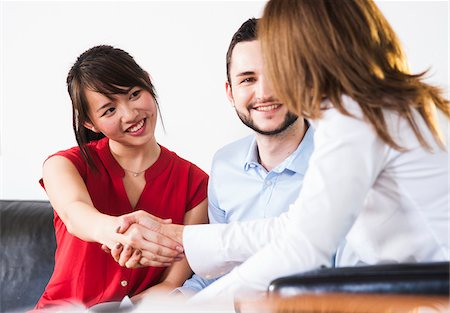 Backview of businesswoman in discussion with young couple and shaking hands, Germany Stock Photo - Premium Royalty-Free, Code: 600-07311408