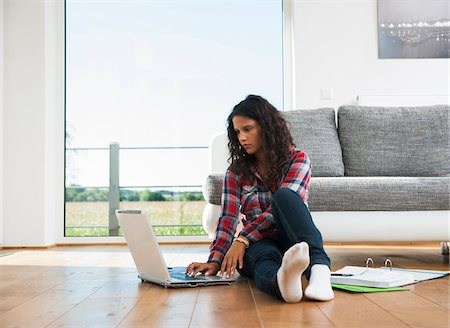 female 16 year old feet - Teenage girl sitting on floor next to sofa, using laptop computer, Germany Stock Photo - Premium Royalty-Free, Code: 600-07311416