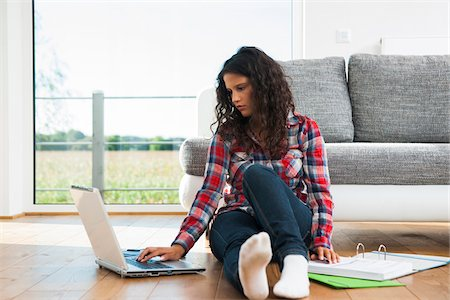 Teenage girl sitting on floor next to sofa, using laptop computer, Germany Stock Photo - Premium Royalty-Free, Code: 600-07311417
