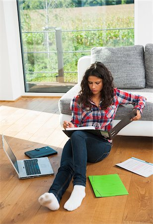 Overhead view of teenage girl sitting on floor next to sofa, reading from binder and using laptop computer, Germany Stock Photo - Premium Royalty-Free, Code: 600-07311418