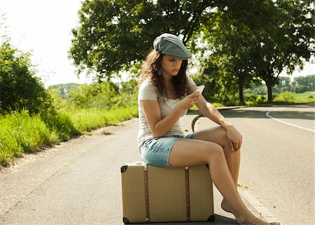 Teenage girl sitting on suitcase on the side of the road, looking at cell phone in summer, Germany Stock Photo - Premium Royalty-Free, Code: 600-07311410