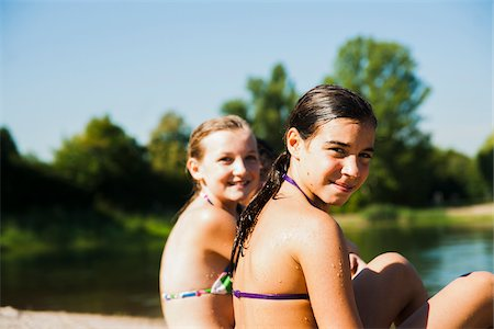 preteen swimsuit - Close-up portrait of two girls sitting on beach at lake, looking over shoulder at camera and smiling, Lampertheim, Hesse, Germany Stock Photo - Premium Royalty-Free, Code: 600-07311412